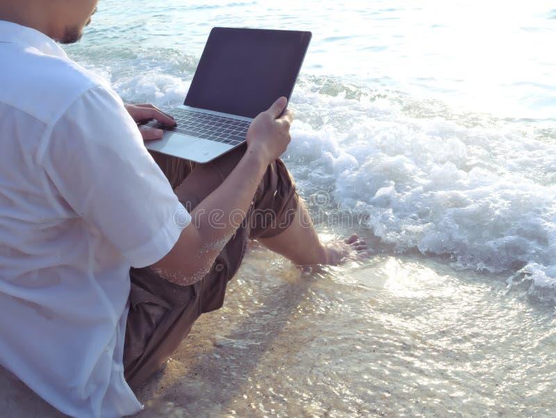 Den kantjusterade bilden av barn kopplade av mannen med bärbar datorsammanträde på den sandiga stranden med mjuka vågor Internet  arkivbild