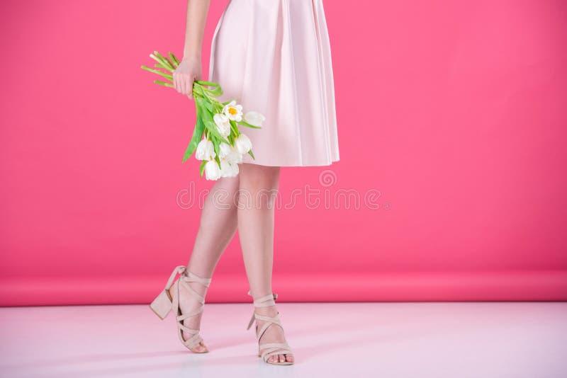 den kantjusterade bilden av flickan i rosa färger klär med buketten av tulpan royaltyfri foto