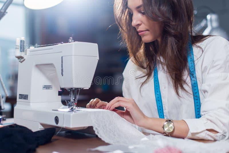 Den kantjusterade bilden av den kvinnliga skräddaren som fint syr, snör åt med symaskinen som sitter i sömnadstudio royaltyfria foton