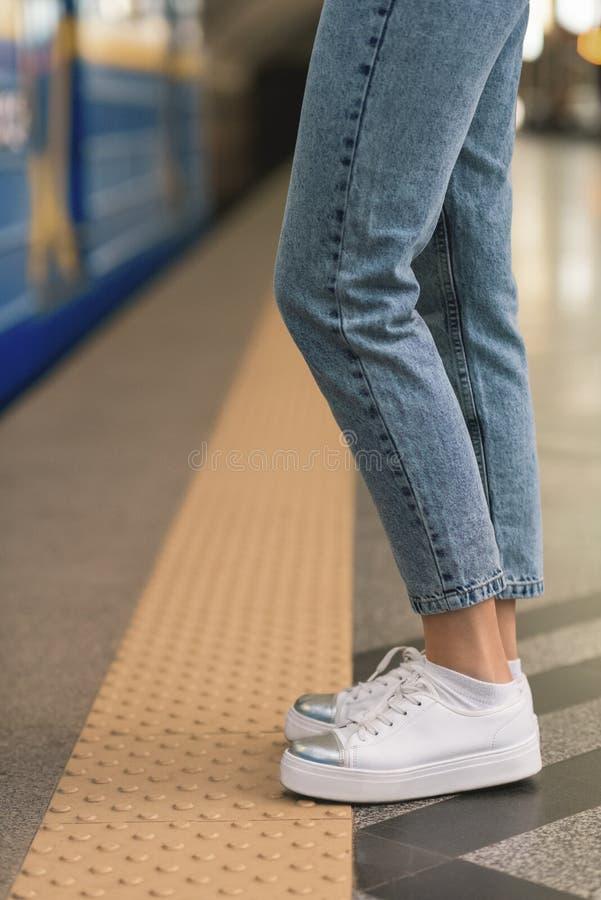 den kantjusterade bilden av kvinnlign lägger benen på ryggen i stilfull jeans och gymnastikskor på gångtunnelstationen royaltyfria foton