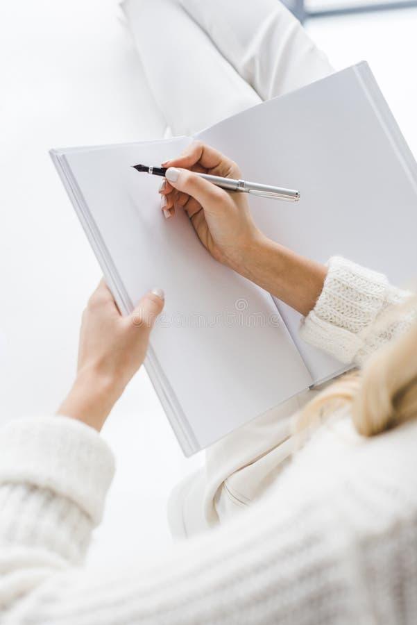 den kantjusterade sikten av affärskvinnan i vit beklär handstil arkivbild