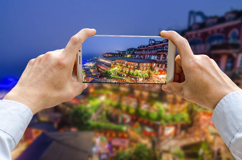 Den kantjusterade sköt sikten av mannens händer som gör fotoet på mobiltelefonkamera, är Jiufen den gamla gatan i den nya Taipei  royaltyfria foton