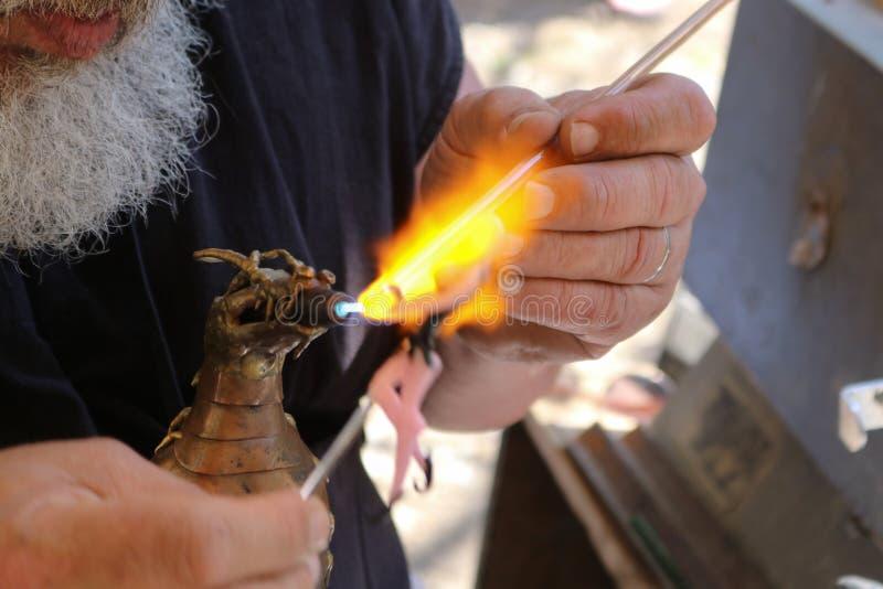 Den kantjusterade vita skäggiga mannen skapar exponeringsglasfen som använder lampworking - smältande glasstavar med draken forma arkivbild