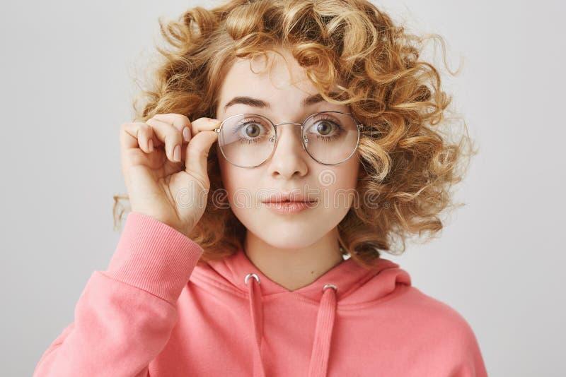 Den karismatiska flickan försöker på nya par av exponeringsglas Stående av den gulliga och roliga kvinnan med lockigt blont hår s royaltyfri bild