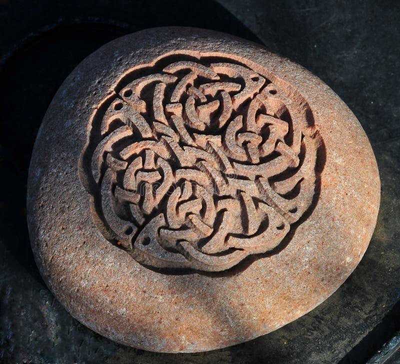 Den keltiska fnurenstenen som snider på cirkuläret, vaggar royaltyfria bilder