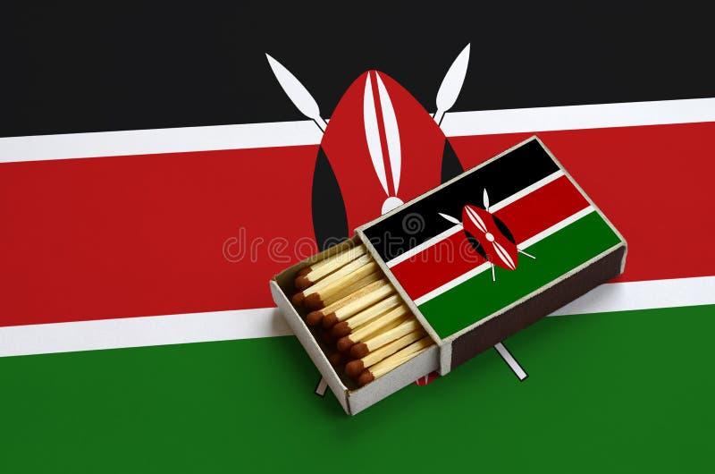 Den Kenya flaggan visas i en öppen tändsticksask, som fylls med matcher och ligger på en stor flagga arkivfoton