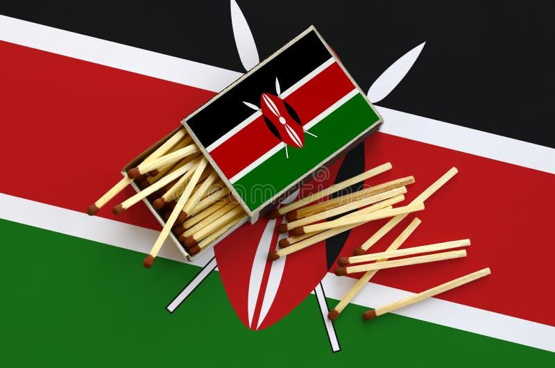Den Kenya flaggan visas på en öppen tändsticksask, som flera matcher faller från och lögner på en stor flagga royaltyfri bild