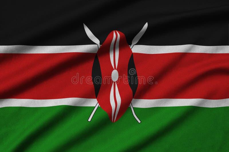 Den Kenya flaggan visas på ett sporttorkduketyg med många veck Baner för sportlag royaltyfria bilder