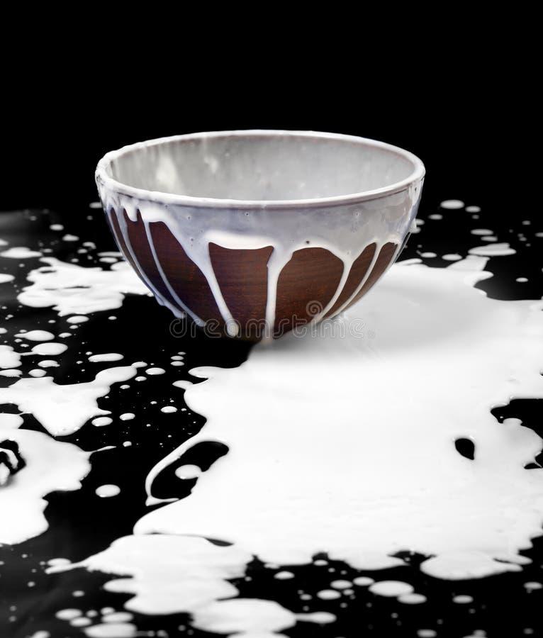 Den keramiska bunken och spillt mjölkar i svart arkivfoton