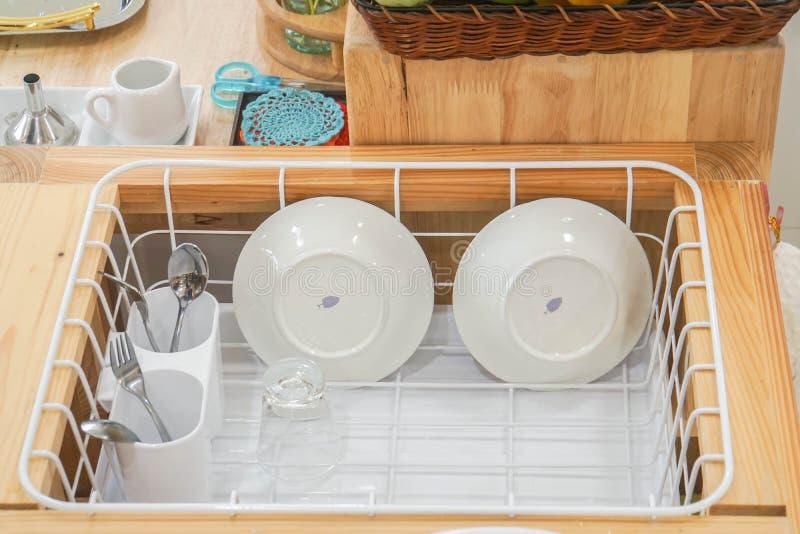 Den keramiska maträtten och rostfritt bestick ställde in i plast- avloppsränna, når de har tvättat sig royaltyfria foton