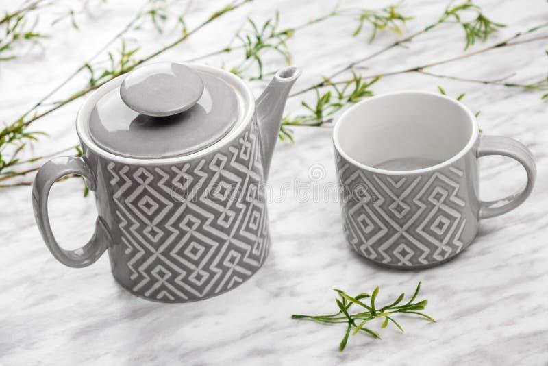 Den keramiska tekannan och koppen marmorerar på yttersida fotografering för bildbyråer