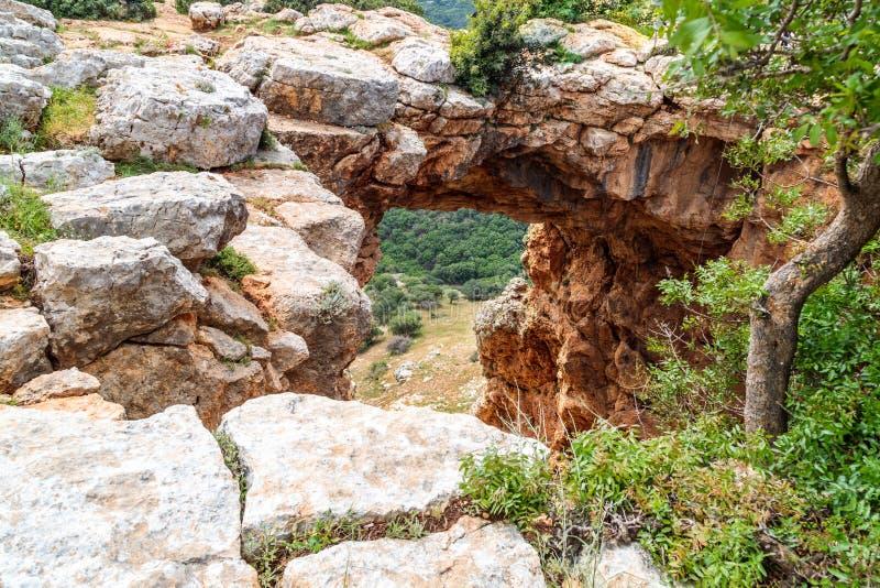 Den Keshet grottan - den forntida naturliga kalkstenbågen som spänner över restna av en grund grotta med att sopa sikter nära den arkivbild