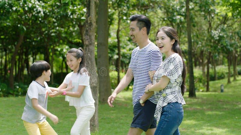 Den kinesiska familjen som tycker om helgaktivitet parkerar in, i sommar fotografering för bildbyråer