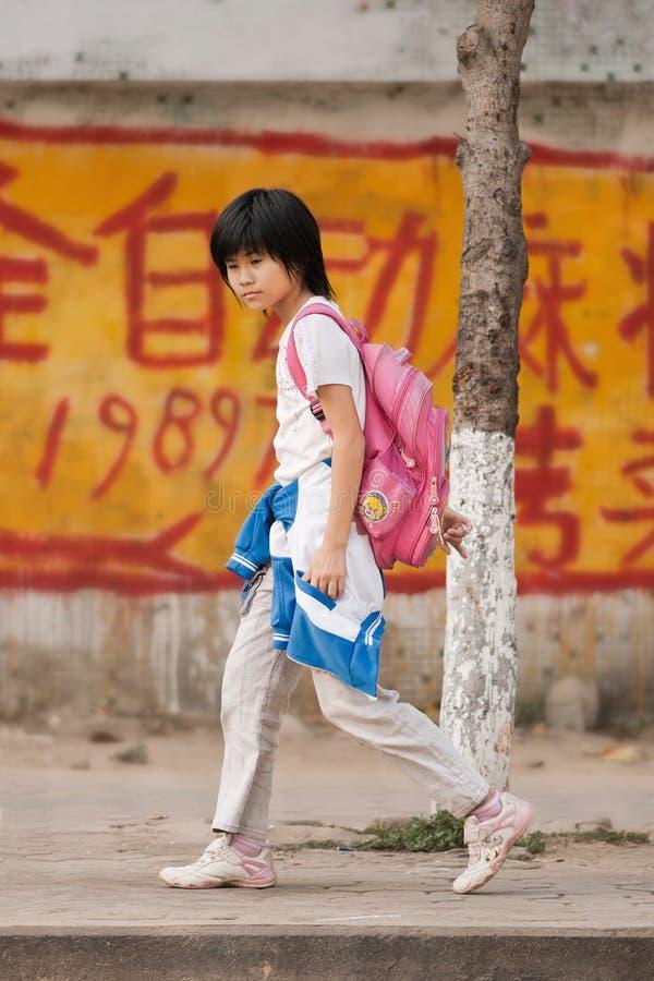 Den kinesiska flickan går tillbaka hem efter skolan, Sanay, Hainan, Kina royaltyfri bild