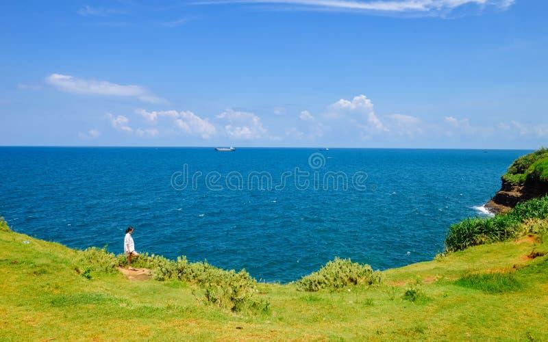 Den kinesiska flickan st?r p? gr?ssl?tten som ser havet royaltyfri foto