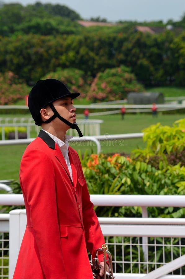 Den kinesiska hornblåsaren i jockeykugghjul börjar det emiratSingapore derbyt på hästkapplöpningen för den Kranji torvaklubban royaltyfri bild