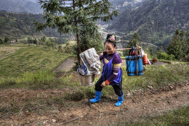 Den kinesiska kvinnabondebonden bär vikten på din skuldra royaltyfri fotografi
