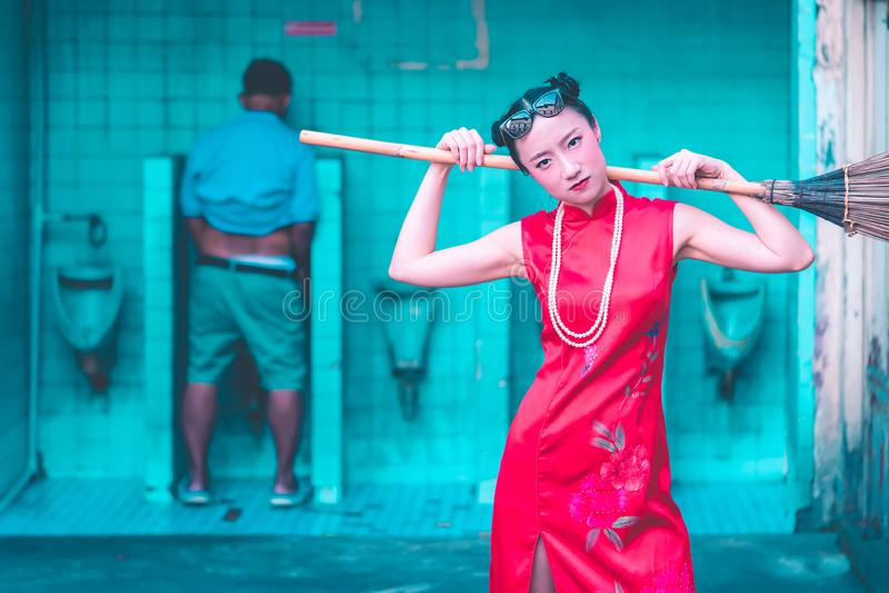 Den kinesiska kvinnan får klar att göra ren upp den manliga smutsiga toaletten arkivfoton
