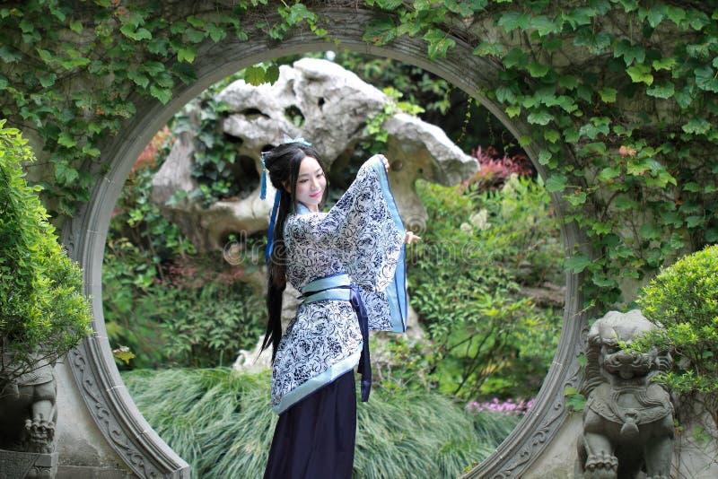 Den kinesiska kvinnan i traditionella blått och vit Hanfu klär anseende i mitt av den härliga porten arkivbilder