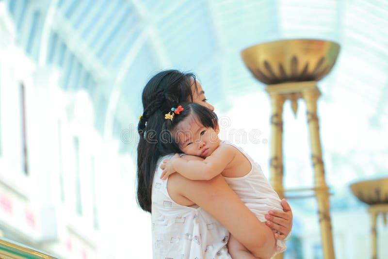 Den kinesiska kvinnan kramar hennes behandla som ett barn flickan på armar arkivbild
