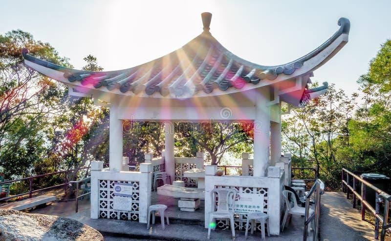Den kinesiska pagoden på familjen går slingan på den Lamma ön i Hong Kong Sceniskt landskap med solstrålar arkivbild