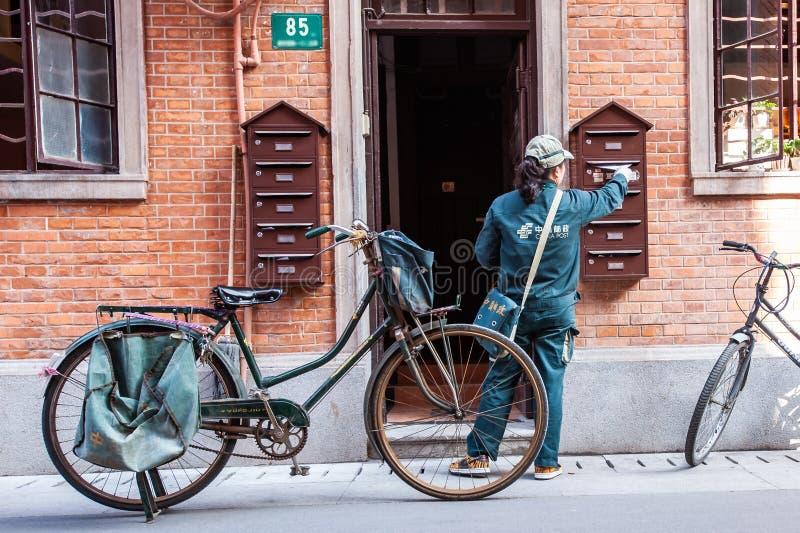 Den kinesiska postwomanen levererar post med cykeln royaltyfri fotografi