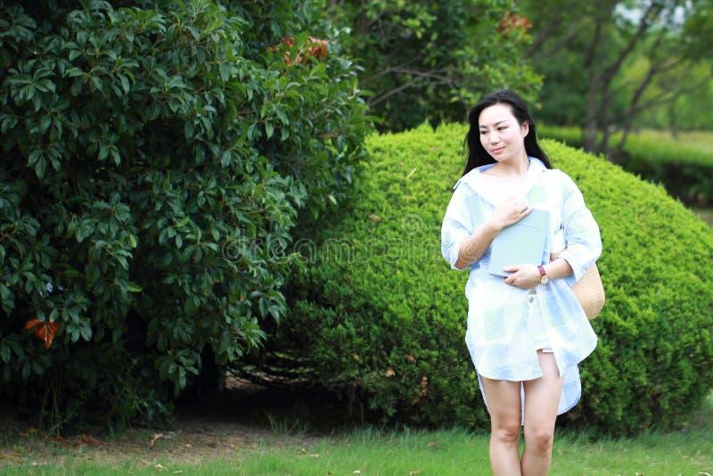 Den kinesiska unga attraktiva studentflickan med långt hår som poserar i universitetsområdegräsplan, parkerar den bärande boken royaltyfri bild