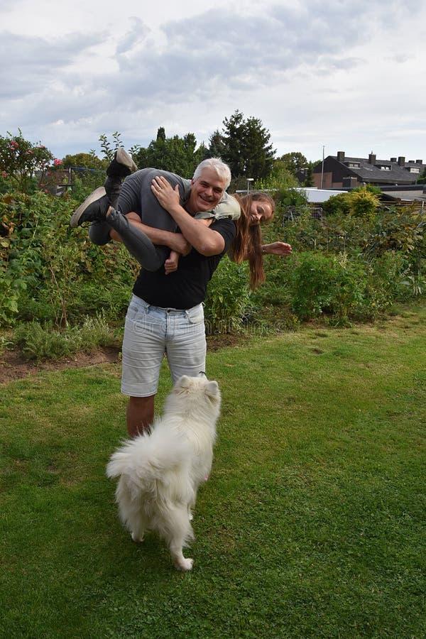 Den kivas fadern och dottern, hunden håller ögonen på förvånat arkivfoton