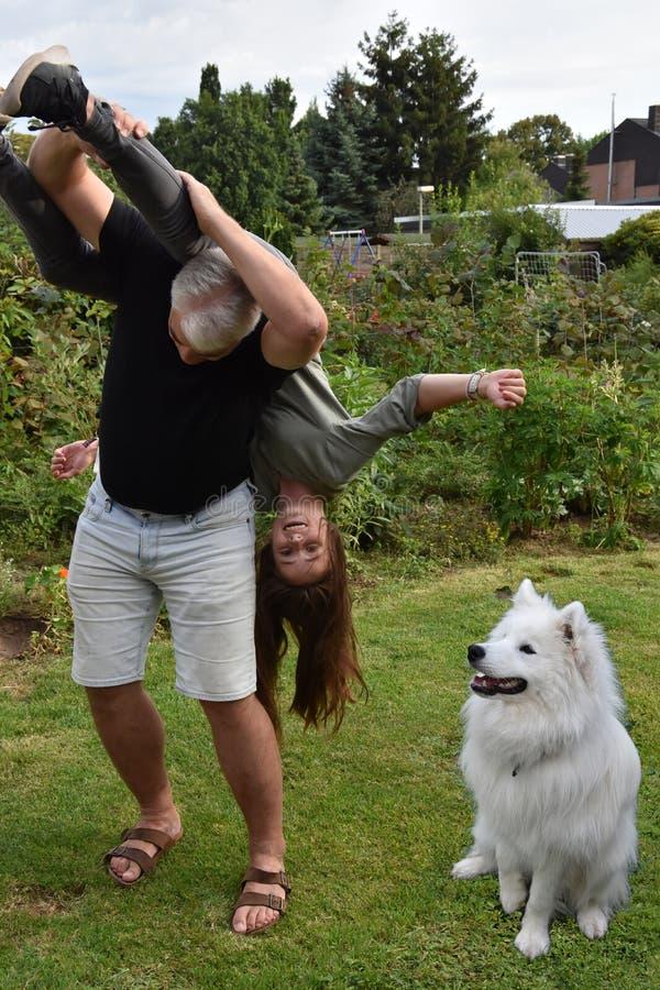 Den kivas fadern och dottern, hunden håller ögonen på förvånat arkivbild