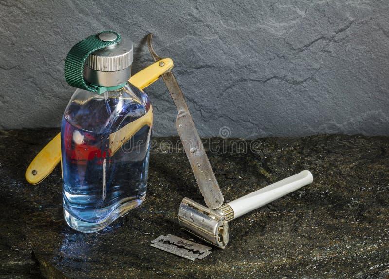 Den klara aftershaveflaskan med den gamla rakkniven på vått stenar textur arkivbild