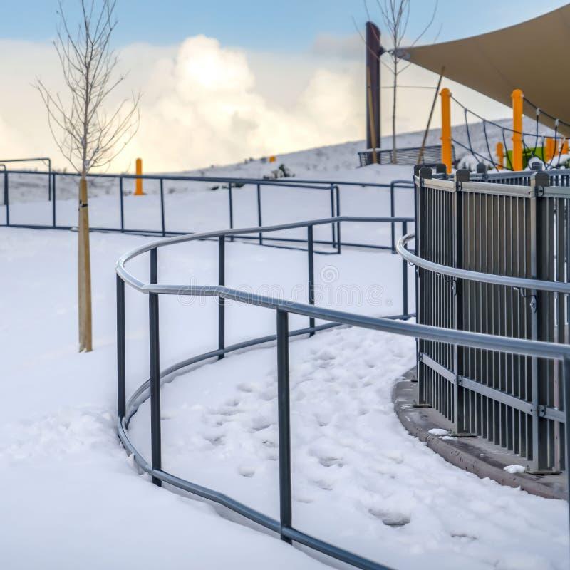 Den klara fyrkanten parkerar i Eagle Mountain Utah mot blå himmel med moln i vinter royaltyfri bild