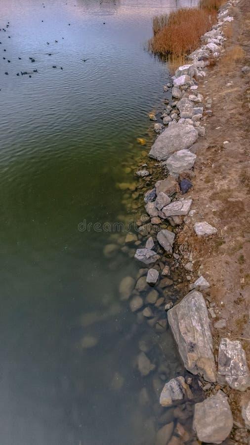 Den klara vertikala sjön med vaggar att fodra kusten och en välvd bro över dess skinande vatten arkivfoton