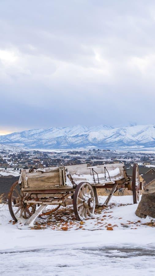 Den klart vertikala red ut trävagnen och enormt vaggar överst av en kulle med insnöad vinter arkivfoton