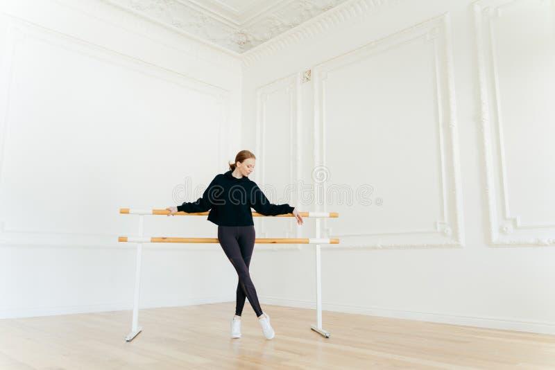 Den klassiska balettdansören har sträckning av genomköraren, ställningar nära balettbarres, bär den svarta tröjan, och damasker,  fotografering för bildbyråer