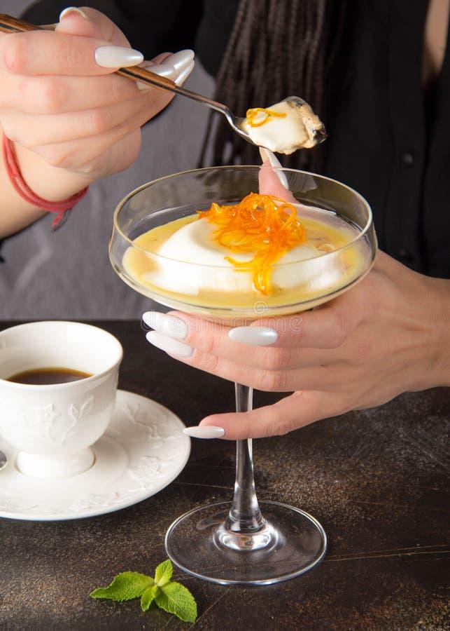 Den klassiska efterrättPanna cottaen i exponeringsglas med orange karamell och kaffe, en kvinna äter med skeden royaltyfria bilder