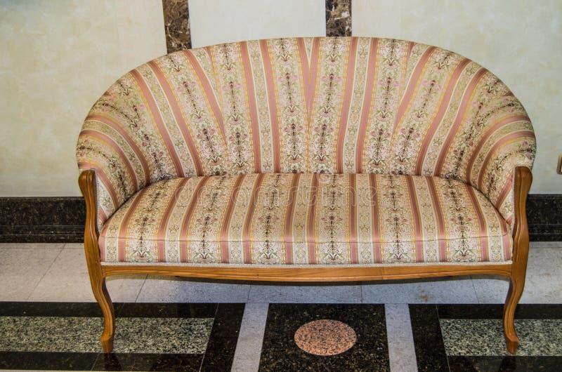 Den klassiska eleganta soffan med textilstoppning och träben som göras i retro stil för tappning, marmorerar golvet och väggar i  arkivfoton