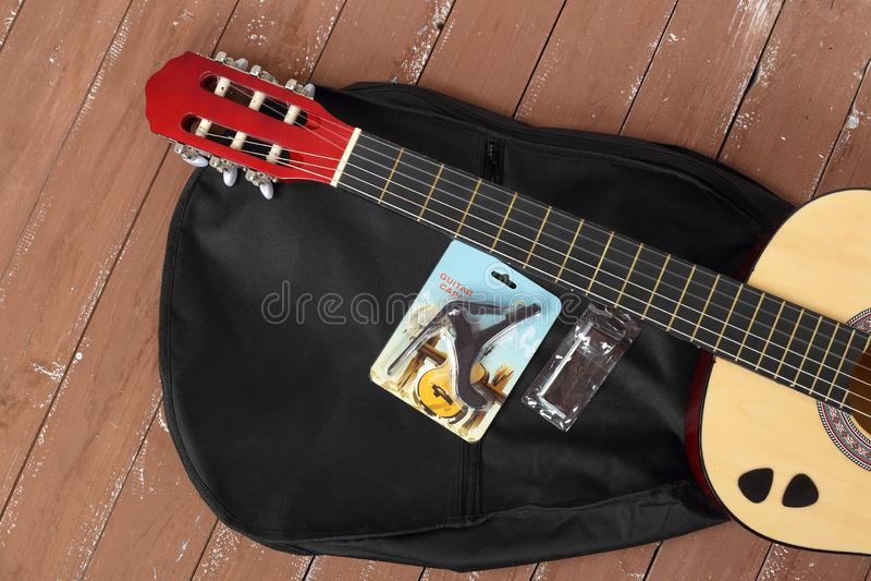 Den klassiska gitarren, fallet, capoen, tangenten, hackor ställde in träbakgrund royaltyfria bilder