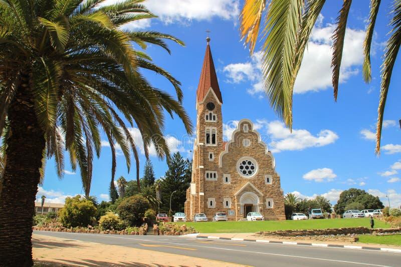 Den klassiska tyska Lutheran kyrkan av Kristus i Windhoek i inställningen av palmträd En av de huvudsakliga dragningarna av stade royaltyfria bilder