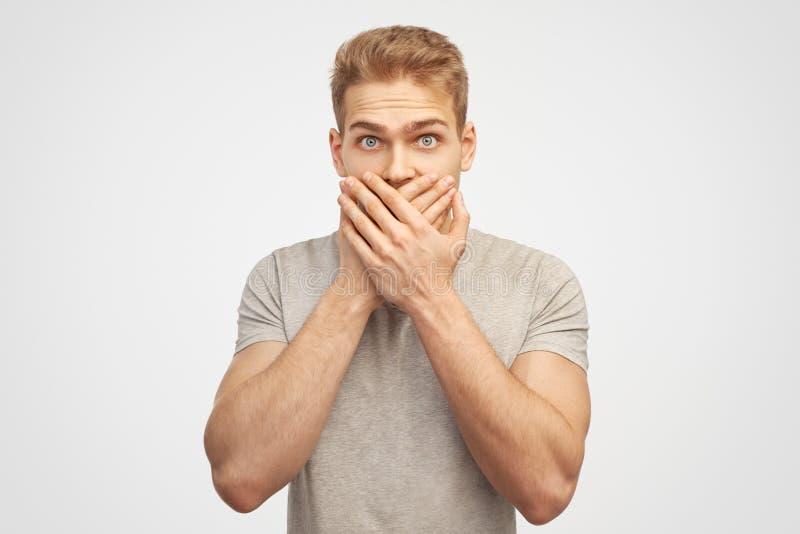Den klentrogna attraktiva mannen täcker munnen, önskar inte att fördela rykten som chockas för att höra plötslig nyheterna från i arkivbild