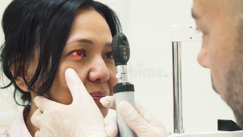 Den klyftiga doktorn skiner en special lampa i patientögonen arkivbild