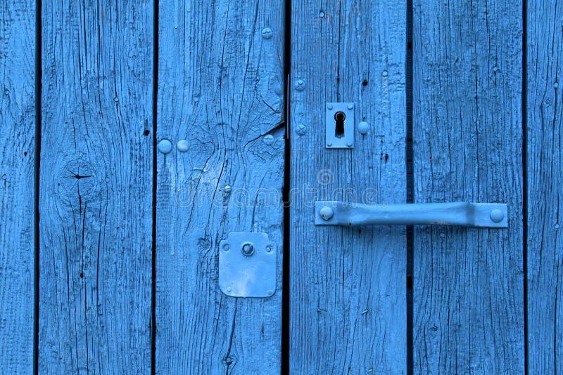 Den knäckte gamla dörren målade blått royaltyfria bilder