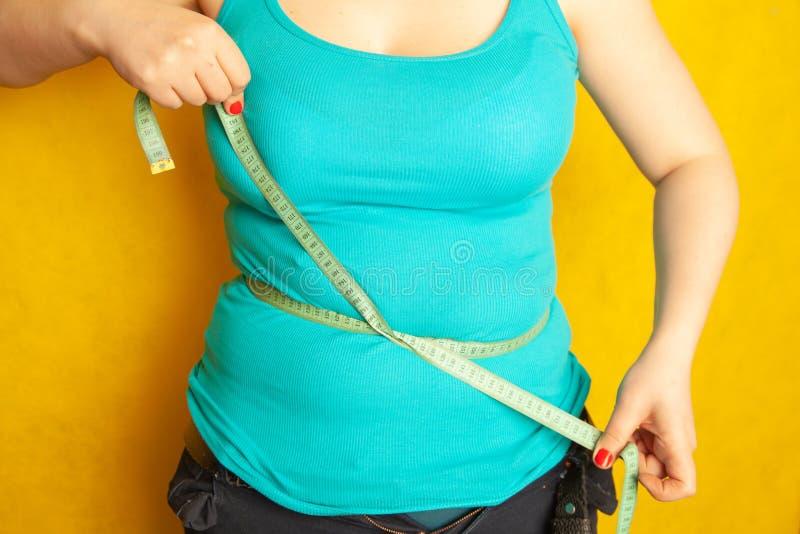 Den knubbiga flickan mäter omkretsen av hennes feta buk vid cmbandet royaltyfria bilder