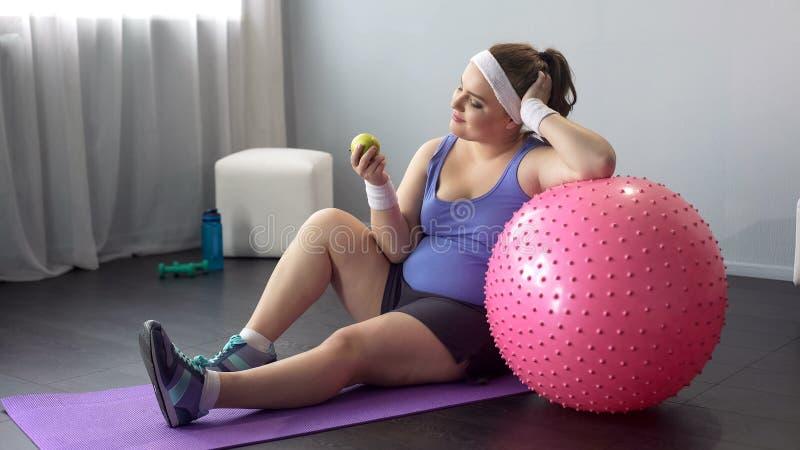 Den knubbiga flickan som äter sund mat, väljer den sunda livsstilen som in går för sportar arkivbild
