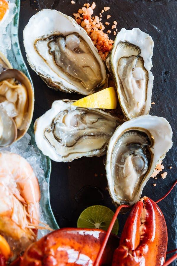 Den kokade humret, nya ostron, räkor, musslor och musslor tjänade som i svart stenplatta royaltyfria bilder