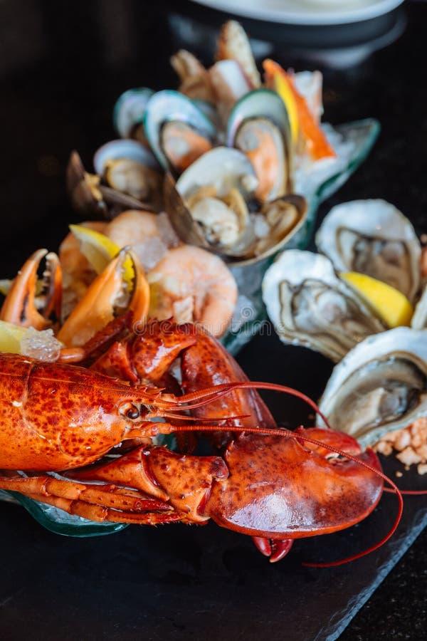 Den kokade humret, nya ostron, räkor, musslor och musslor tjänade som i svart stenplatta arkivfoton