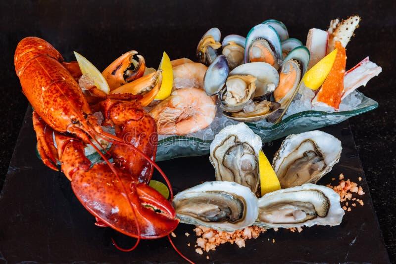 Den kokade humret, nya ostron, räkor, musslor och musslor tjänade som i svart stenplatta arkivfoto