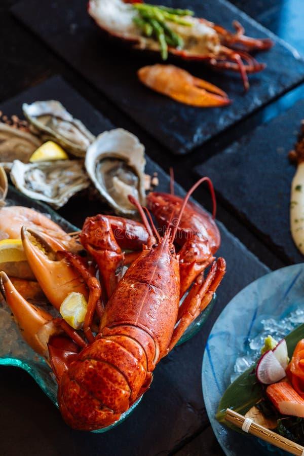 Den kokade humret, nya ostron, räkor, musslor och musslor tjänade som i svart stenplatta royaltyfri bild