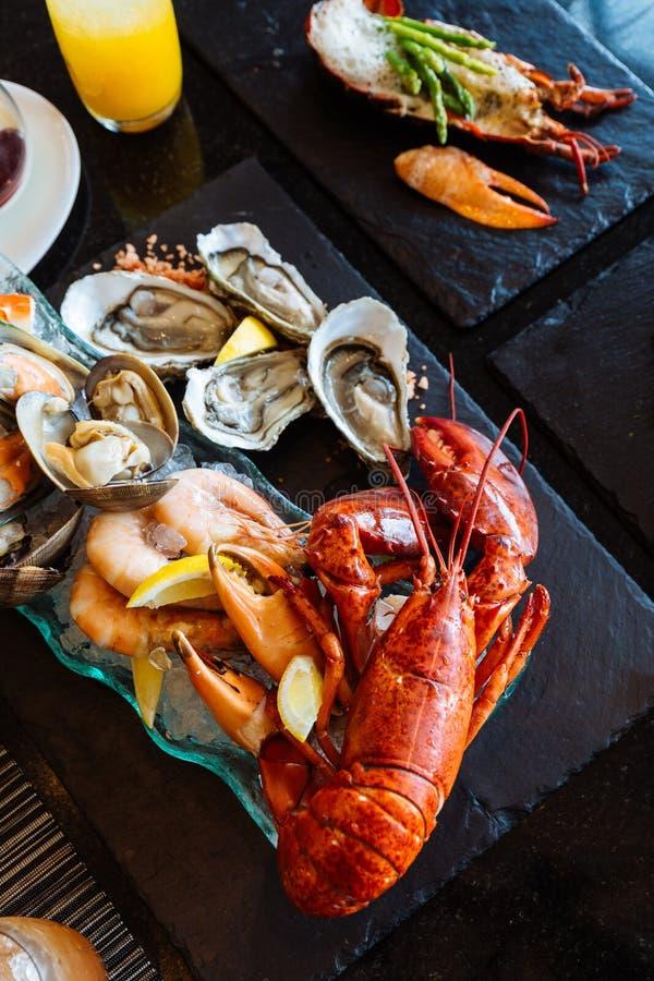 Den kokade humret, nya ostron, räkor, musslor och musslor tjänade som i svart stenplatta royaltyfri fotografi