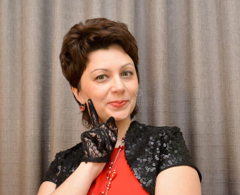 Den kokedda kvinnan av genomsnittliga år i svarta openwork handskar och en bolero royaltyfria bilder