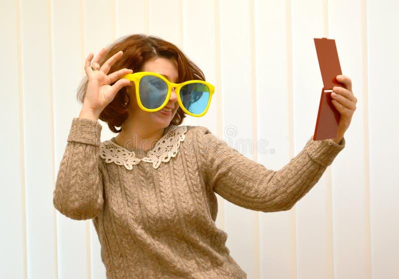 Den kokedda kvinnan i stor solglasögon ler och att se henne i en spegel arkivfoton